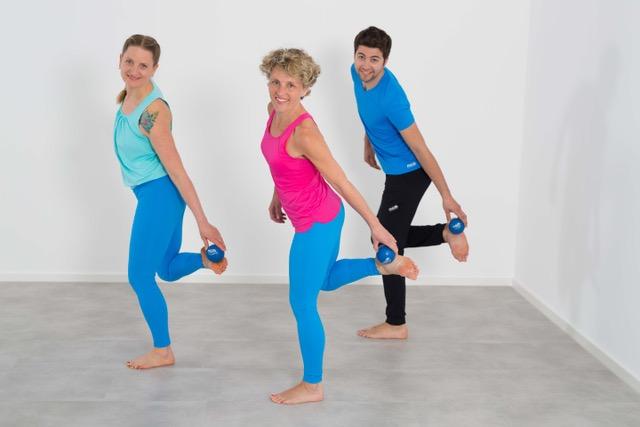 Zwei Frauen und ein Mann, die ihre Füße mit Faszienbällen behandeln und Faszienyoga ausüben