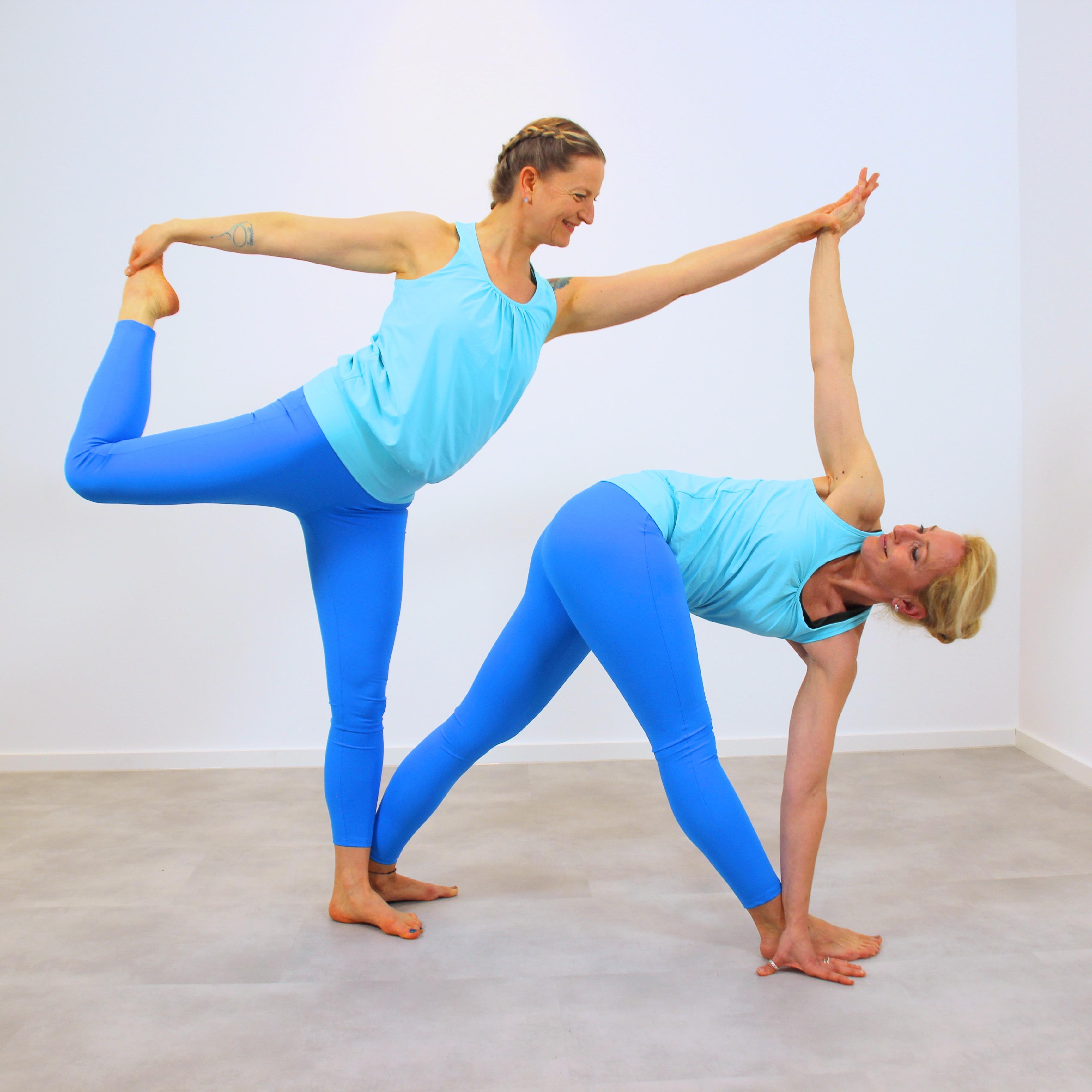 Zwei Frauen in Yoga Asana Tänzer und gedrehtes Dreieck