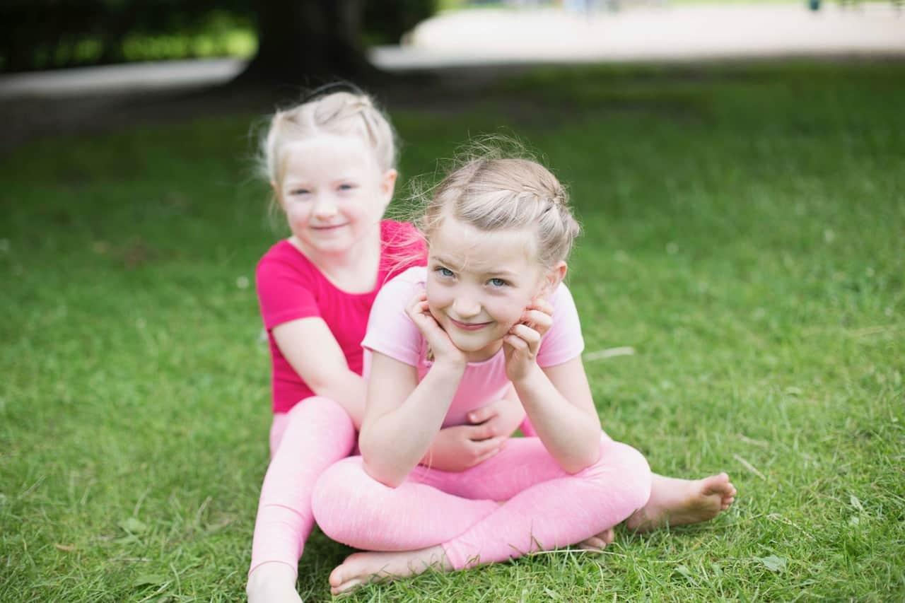 Zwei kleine Mädchen auf einer Wiese in Kinderyoga Kleidung in rosa