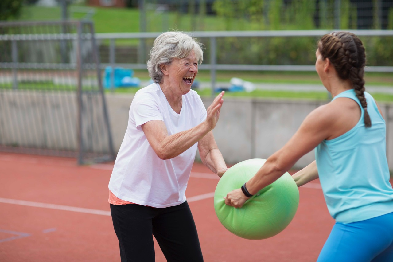 Lachende ältere Teilnehmerin mit Ball in der Reha-Sportgruppe Brustkrebs