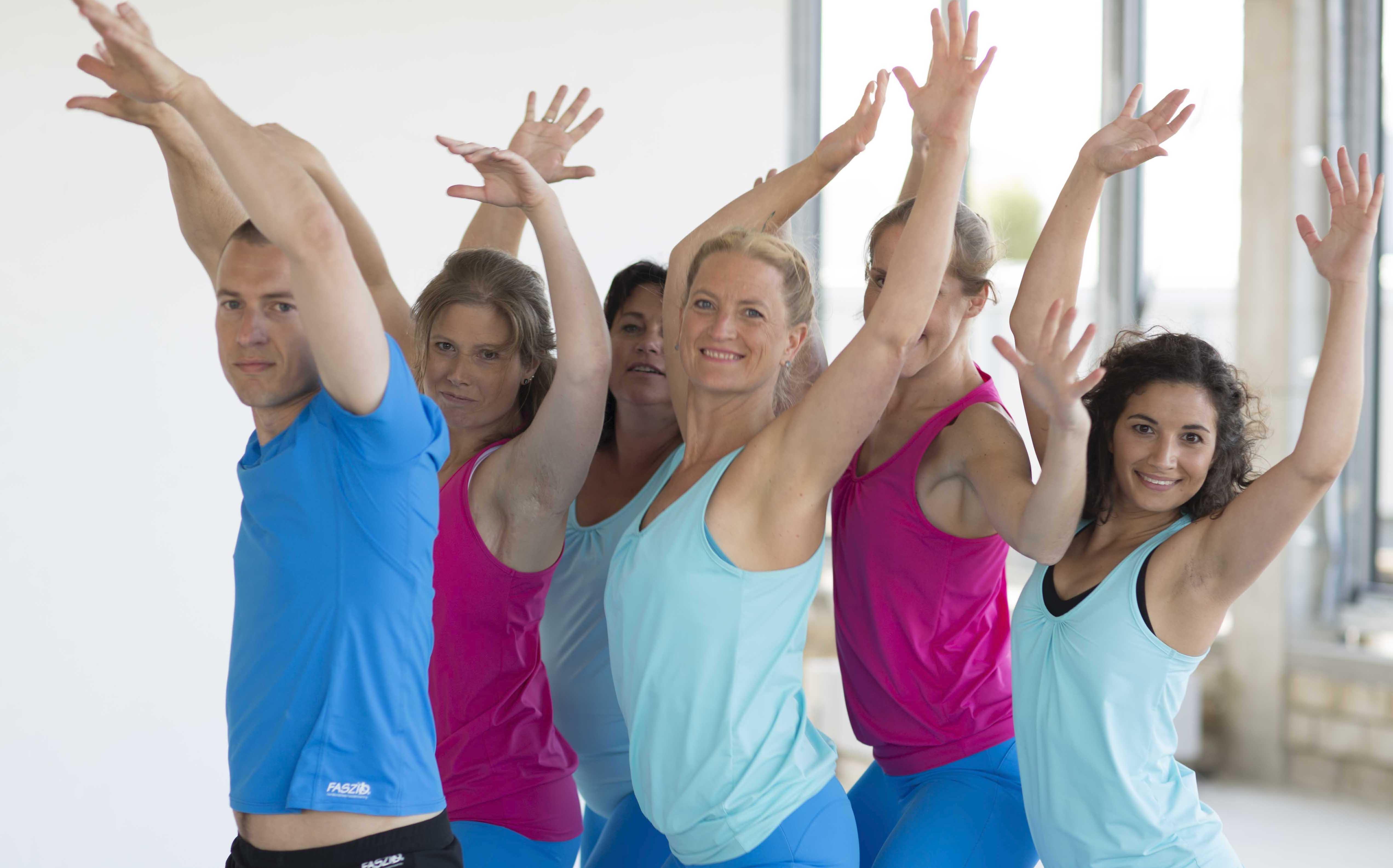 Gruppe an Menschen, die ihre Hände in die Höhe heben und im YogaDancing tanzen