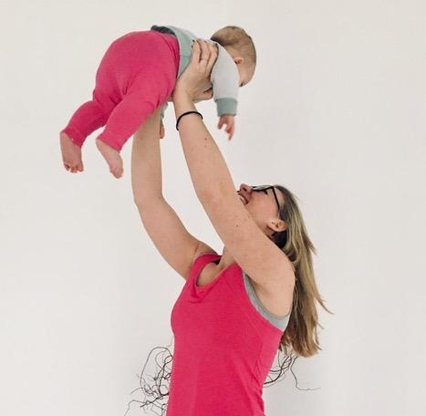 Frau, die ihr Baby nach der Geburt in die Höhe streckt
