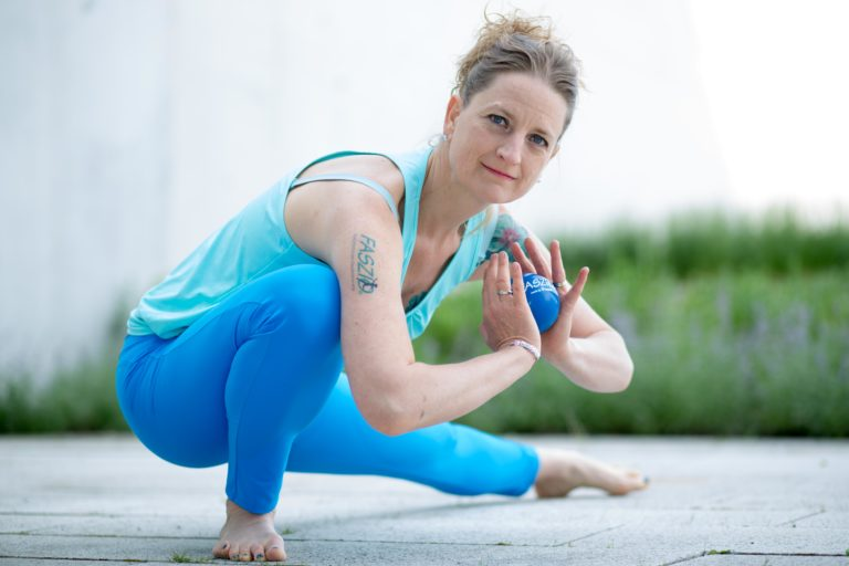Frau in Yoga Asana mit Faszienball in der Hand und FASZIO Tatoo auf dem Arm