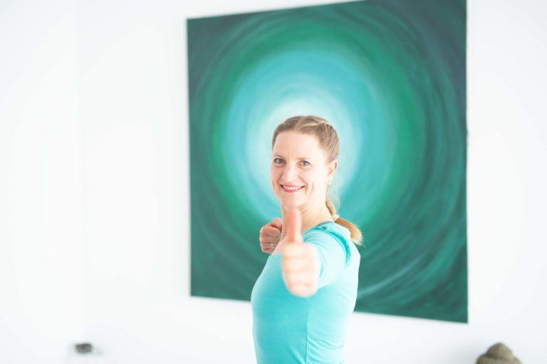 Miriam Wessels, die in die Kamara lächelt vor dem Bild aus dem Bewegungsraum der FYTT location Hamburg Groß Borstel Eppendorf