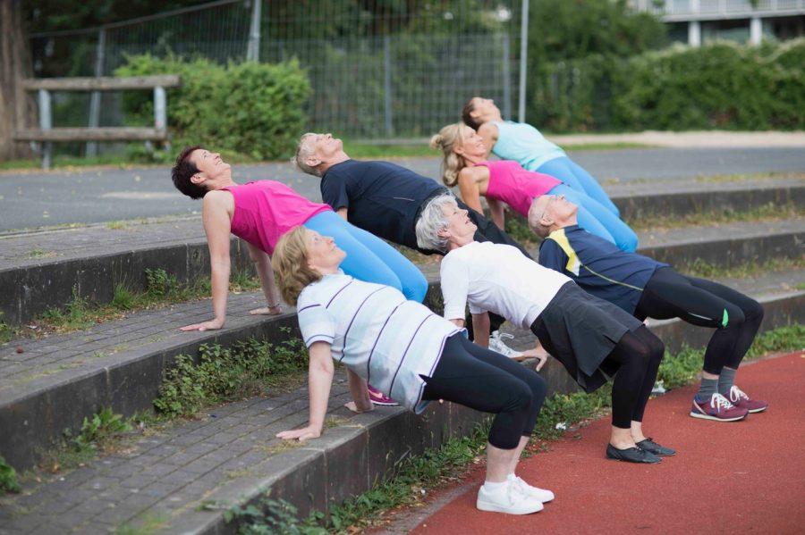 Gruppe von Menschen in Yoga-Haltung in der Reha-Herzsportgruppe